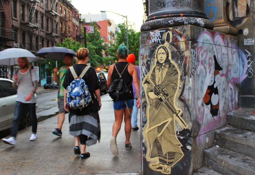 beautiful wheat paste up of a native american on the public art gallery buildning on the corner of bowery and spring street in soho in new york city, street art, graffiti