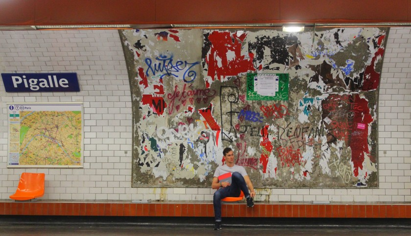 Pigalle subway station in Paris with ute boy posing in front of street art, public space take over