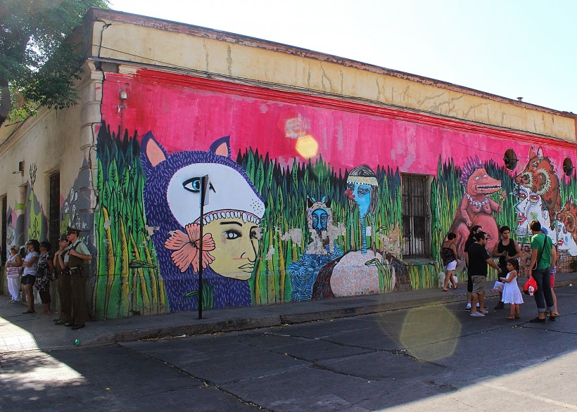 colorful and dreamlike mural in barrio yungay in santiago de chile, public space take over and street art covered walls, graffiti and tags and throws