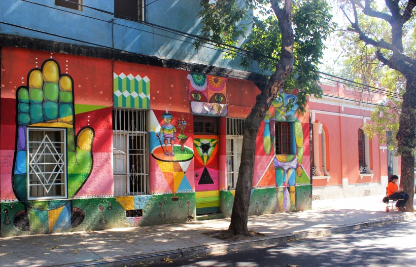 beautiful and colorful mural in barrio bellavista in santiago de chile, public space take over with street art and graffiti with tags and throws