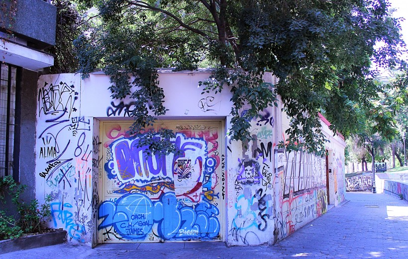 super bombed walls with tags and throws and graffiti in barrio lastarria in santiago de chile, public space take over, street art